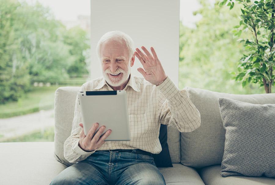 Grandfather saying hello to family via computer